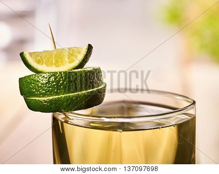 Alcohol drink. On wooden boards is glass with alcohol green transparent drink. A drink number four cocktail green tea is decorated with lime. Country life. Light background.