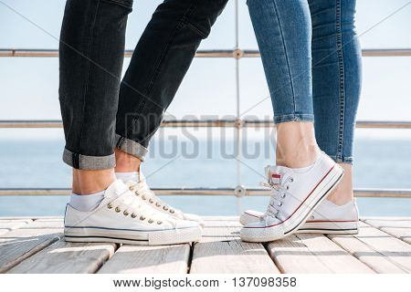 Young couple in love standing in gumshoes at the seaside