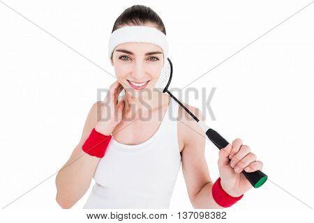 Female athlete playing badminton on white background