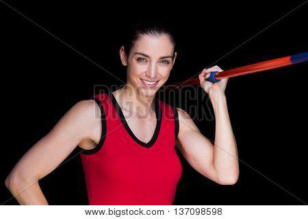 Female athlete throwing a javelin on black background