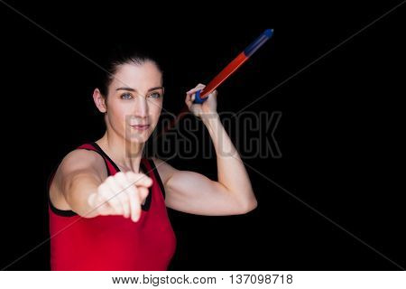 Female athlete throwing a javelin on black background