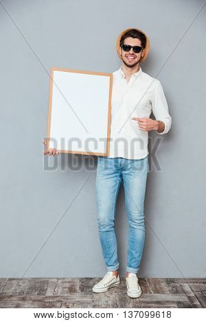 Cheerful young man holding blank white board and pointing on it over grey background