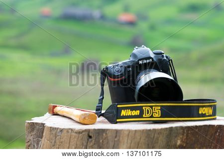 BRASOV, ROMANIA - MAY 24, 2016: NIKON D5 DSLR  left on a log