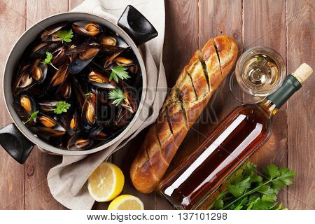 Mussels in copper and white wine on wooden table. Top view