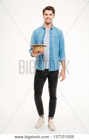 Happy attractive young man holding hat and asking for money over white background