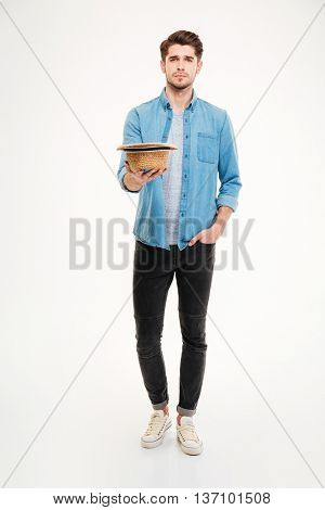 Full length of poor young man with hat standing and asking for money over white background