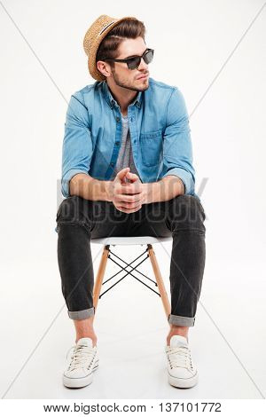 Pensive young man in hat and sunglasses sitting on chair and thinking over white background