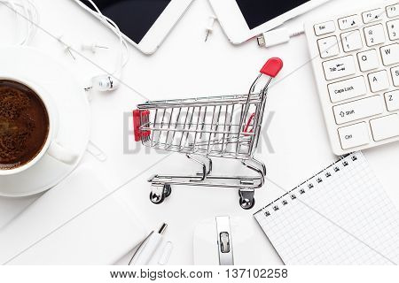 shopping online concept. small red trolley, different gadgets and stationery on the white office table