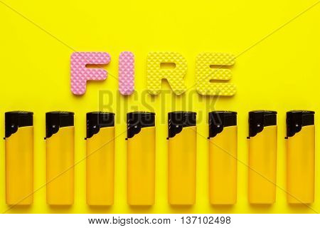 disposable plastic lighters and word fire on yellow background