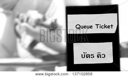 Queue Ticket Box and background camera customer service woman abstract blur black and white picture.