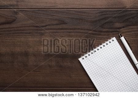 blank notebook and white pen on the brown wooden table