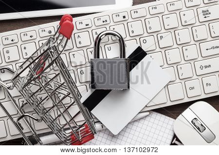 shopping online safely concept. small red trolley, padlock, credit card and computer on the table