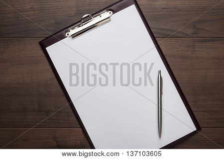 view from above. brown wooden office table with notepad and pen