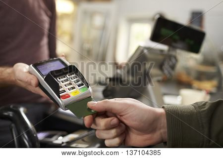 Customer makes credit card payment over counter at a cafe