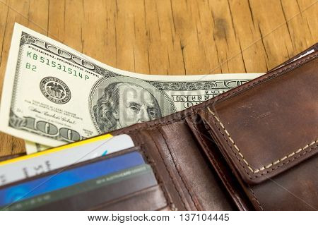 Leather wallet with dollar bills falling out