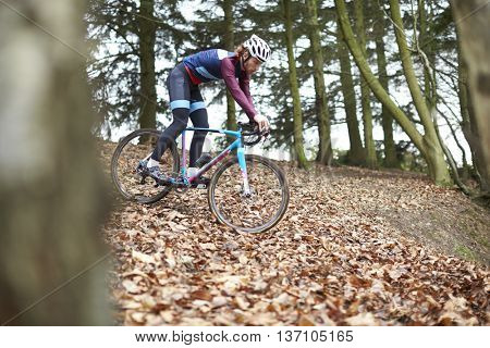 Cross-country cyclist descending a slope, selective focus