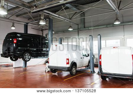 SUV big service station, black minibus raised up on lift. Front view on line of three cars in garage on service maintenance, two white pickups stay in stables, black minibus lifted up