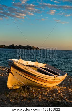 Boat on a beach at sunset with ruins of old roman fortress in backround, Sithonia, Greece