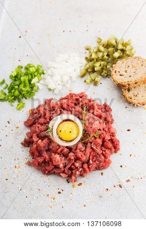 Beef tartare served with bread minced onions and cucumbers