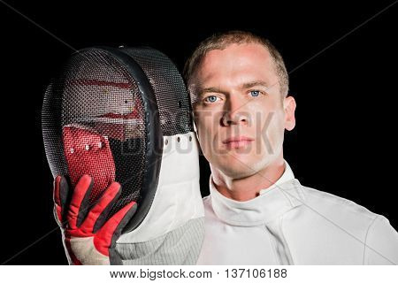 Portrait of swordsman holding fencing mask on black background