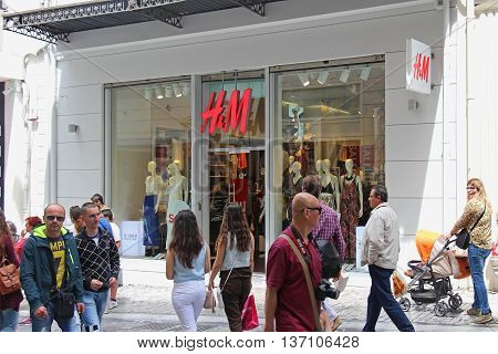 ATHENS GREECE - May 02; Famous Ermou street shopping district with H&M store and people walking around in Athens Greece - May 02 2015; Ermou street is traditional walking street famous for shopping among tourists and locals.