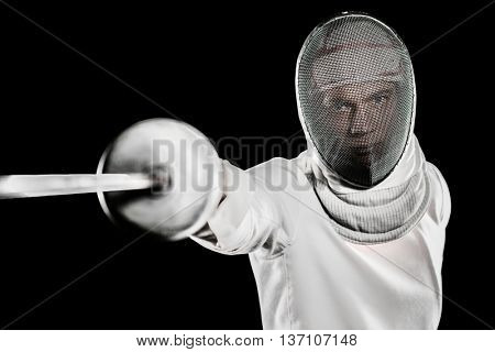Man wearing fencing suit practicing with sword on black background