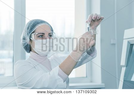 Woman scientist in a white protective clothing conducts research in a lab