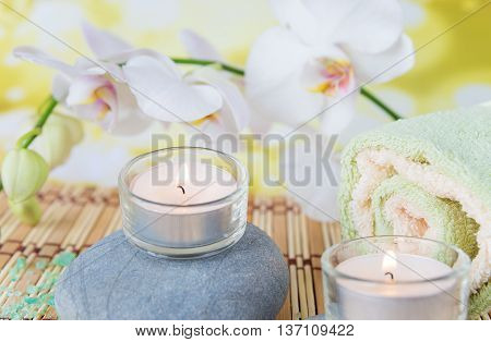 Spa concept: bath towels two lighted candles on a wild rock and a branch of white orchid