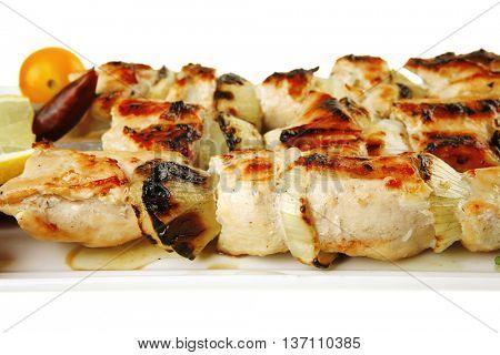 shish kebab on white platter with vegetables
