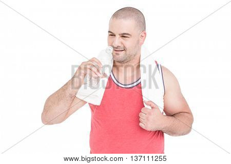 Athlete with towel around neck and water bottle in hand on white background
