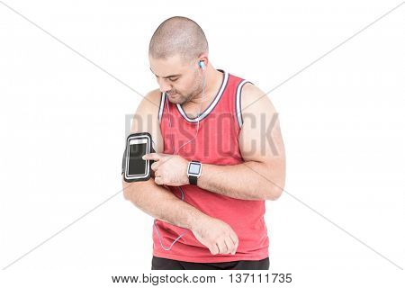 Athlete listening music and touching armband for smartphone