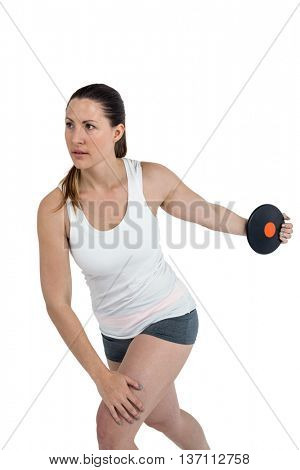 Determined female athlete playing discus throw on white background