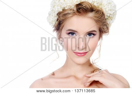 Beauty portrait. Smiling young woman with natural make-up and wreath of white flowers on her head. Summer, spring inspiration. Beauty, fashion, cosmetics. Isolated over white.