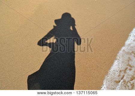 Woman with hat shadow on the beach sand