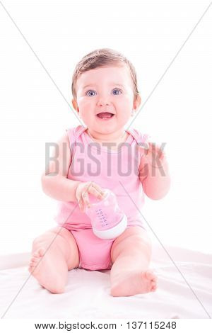 Beautiful baby girl with pink baby bottle.