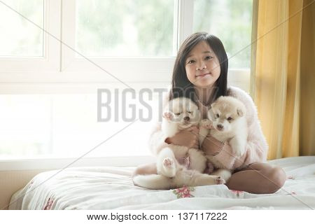 Little asian playing with siberian husky puppies on the bedvintage filter