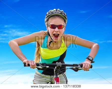 Bikes cycling girl. Girl rides bicycle against blue sky with loud cry. Girl in cycling. Cycling is good for health. Cyclist looking up on blue sky.