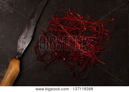 extra hot red chili pepper strings, threads on metal background