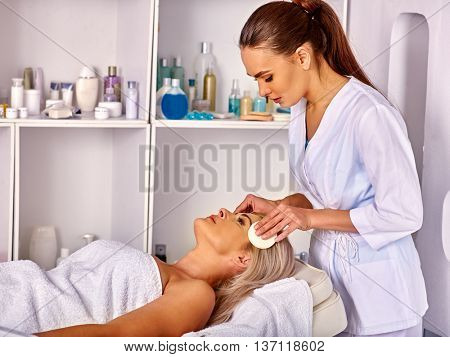 Portrait of woman middle-aged take face cleaning in spa salon. Salon procedure for middle-aged woman .