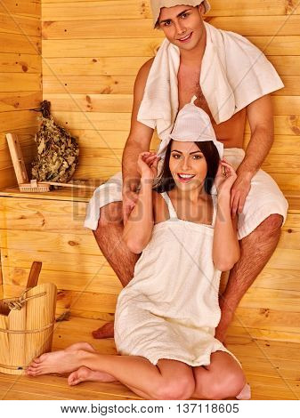 Man wearing sauna hat relaxing at sauna with her girls.