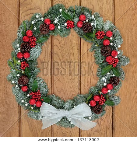 Christmas wreath with white bow, red bauble decorations, holly, pine cones, mistletoe and snow covered blue spruce fir over oak wood front door background.