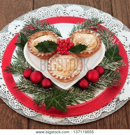 Christmas mince pie cakes with holly, snow covered winter greenery and bauble decorations over oak  background.
