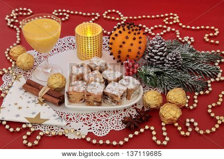 Christmas sweet food with stollen cakes, egg nog, foil wrapped chocolates, spices, candle, orange pomander and decorations on a red background.