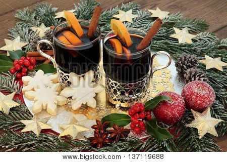 Christmas mulled wine, snowflake gingerbread biscuits, with gold star decorations, spices, fruit, holly and snow covered fir over oak background.