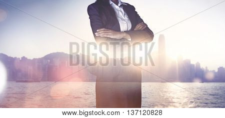 Artistic double exposure of a confident successful businesswoman standing with folded arms in front of a waterfront skyline cityscape of a metropolis with skyscrapers backlit by a glowing sun flare