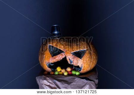 orange halloween pumpkin with scary face and silver pail as hat with colorful dragee candies in mouth on paper on grey background