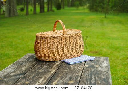 Picnic basket with blue white checkered tablecloth on wooden table. Summertime park lawn in the background