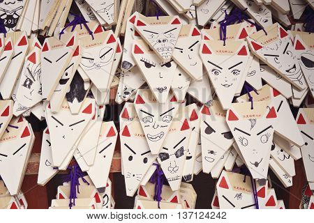 KYOTO, JAPAN - APRIL 29, 2016 : Ema prayer tablets with unique fox-shaped boards at Fushimi Inari Taisha Temple in Kyoto. Pray for luck, wealth, happiness, health, fortune, protection.