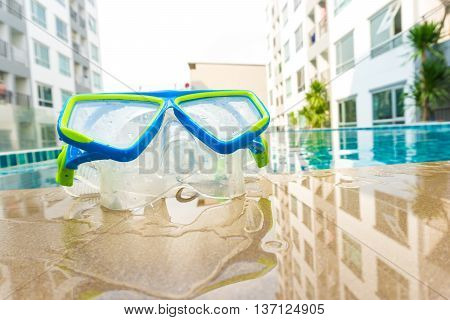 Snorkeling Mask On Swimming Pool Backgeound With Condominium