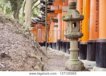 KYOTO, JAPAN - APRIL 29, 2016 : The lamp post and orange Torii gates in Fushimi Inari shrine, one of famous landmarks in Kyoto, Japan